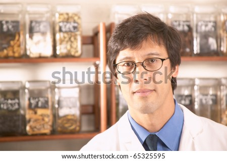 Asian male herbalist doctor in front of Chinese medicinal herbs