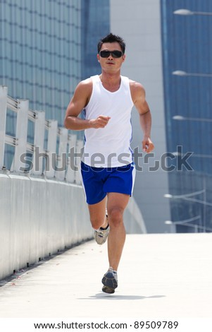 Asian male jogging with skyscraper in background - stock photo