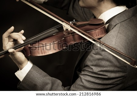 Asian male Musician plays Violin on Dark Background - stock photo