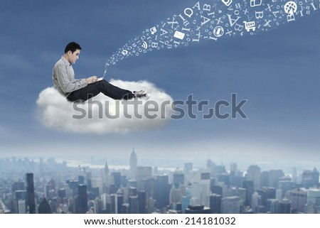 Asian male student sitting on a cloud under blue sky with laptop