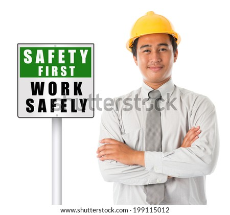 Asian male worker wearing a hardhat smiling and looking at camera, arms crossed standing beside safety first sign board, isolated on white background.