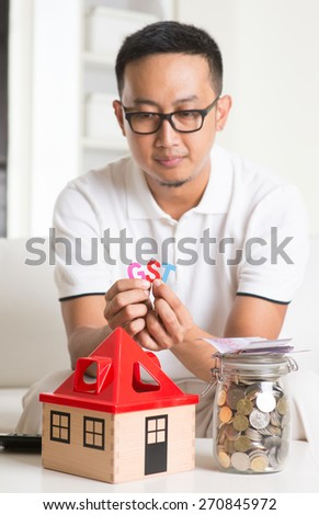 asian male worried about property taxes - stock photo