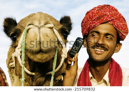 Asian man and camel in the desert with communication, Rajasthan, India. - stock photo