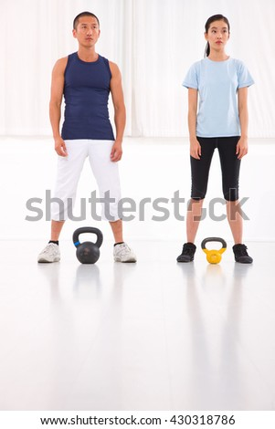 Asian man and woman doing kettle bell crossfit exercise - stock photo
