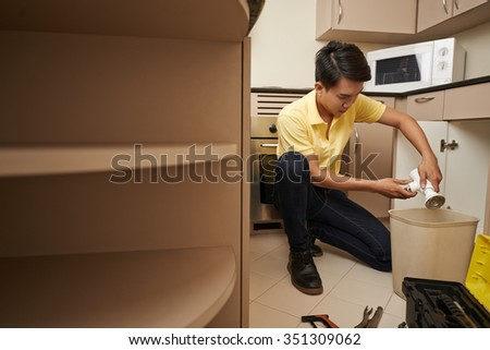 Asian man cleaning sink drain in home kitchen - stock photo