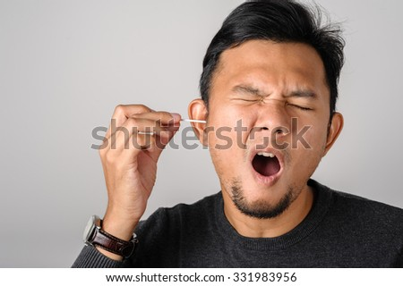 asian man cleans his ear with cotton swab - stock photo