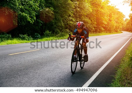 Asian man cycling on the road morning sunrise