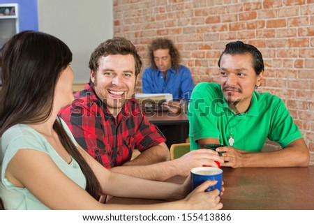 Asian man drinking coffee with Caucasian friends in cafe