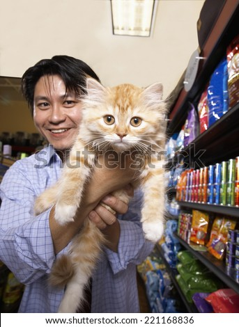 Asian man holding cat in pet store - stock photo