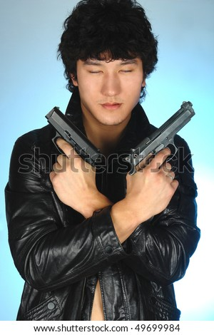 asian man holding two guns in hands - stock photo