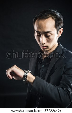 Asian man in a white shirt with grey suit in studio lighting in grey background