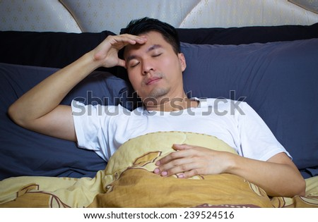 Asian man in bed suffering insomnia, headache and sleep disorder thinking about his problem - stock photo
