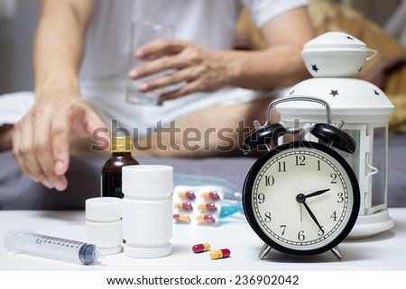 Asian Man in bed with tablets and water suffering insomnia, hangover and headache at night - stock photo