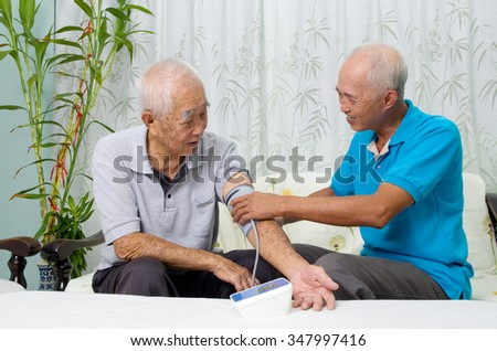 Asian man is checking taking his father's blood pressure. - stock photo