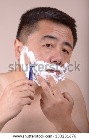 Asian man is shaving in the morning.