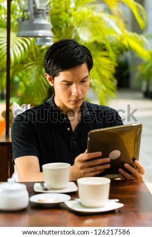 Asian man is sitting in a bar or cafe outdoor and is surfing the internet with a tablet computer - stock photo