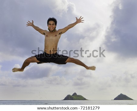 asian man jumping at the beach in hawaii