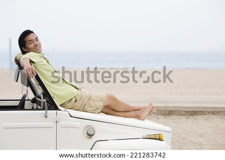 Asian man laying on car hood - stock photo