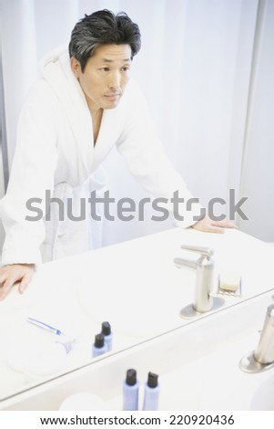 Asian man looking in bathroom mirror - stock photo