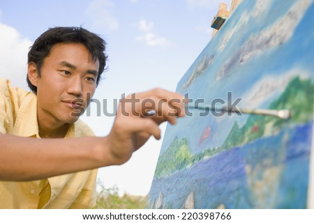 Asian man painting at easel outdoors - stock photo