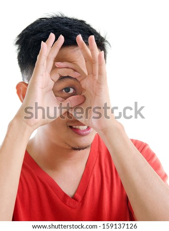 Asian man peeping through fingers hole, isolated on white background