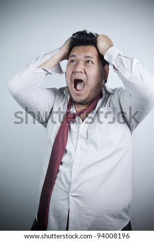 Asian man, pulling his hair, making very stressed expression on his face - stock photo
