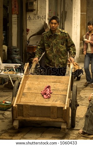 Asian man pushing a wooden Wagon