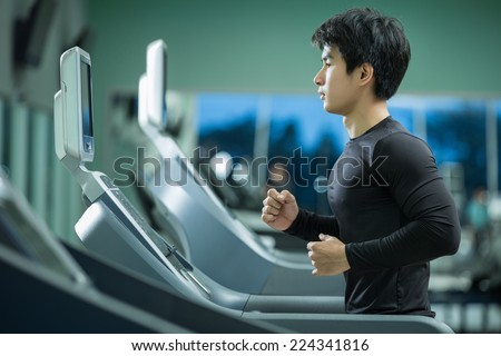Asian man running on the treadmill in the gym