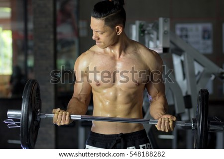 Asian man show bodybuilder in gym.
