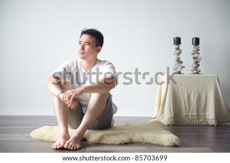 Asian man sitting on the floor thinking - stock photo