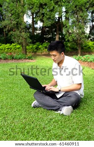 asian man using computer outdoor - stock photo