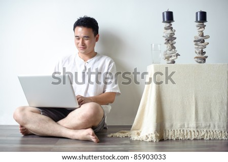 Asian Man Using Laptop Sitting on the floor - stock photo
