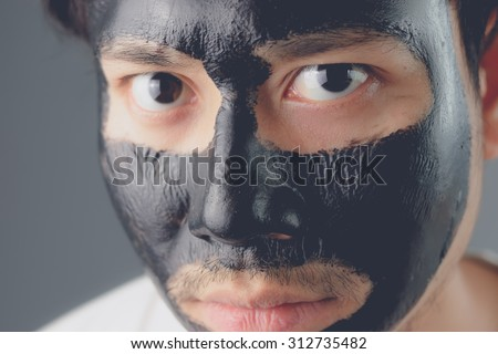 Asian man with black charcoal mask.