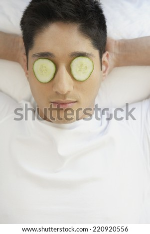 Asian man with cucumber slices on eyes - stock photo