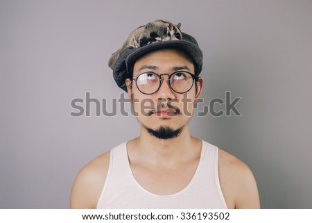 Asian man with flat cap and tank top is looking up above.  - stock photo