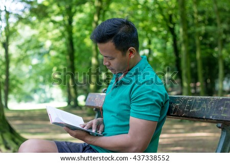 asian man with reading a book and listening music in the  park