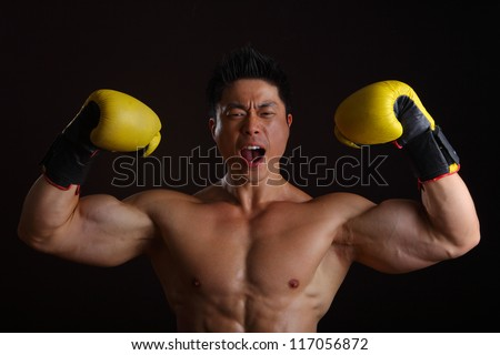 Asian Man with yellow boxing gloves posing for the camera - stock photo