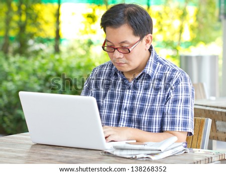 Asian man working with laptop. - stock photo