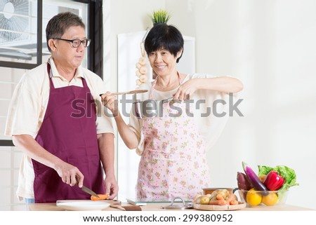 Asian mature couple cooking meal at kitchen. Seniors living lifestyle at home. - stock photo
