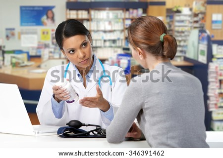 Asian medical doctor with patient woman over pharmacy background. - stock photo