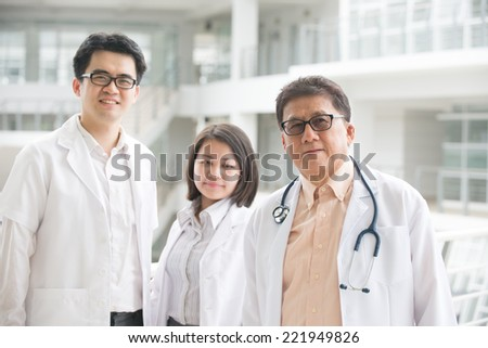 Asian medical team of doctors standing inside hospital building  - stock photo