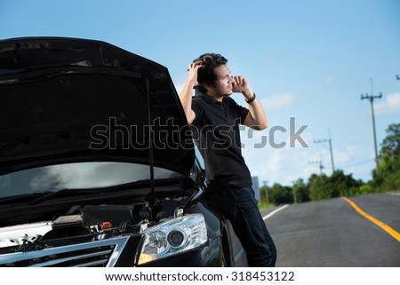 Asian men are calling for help because his car was uninsured at the wayside - stock photo