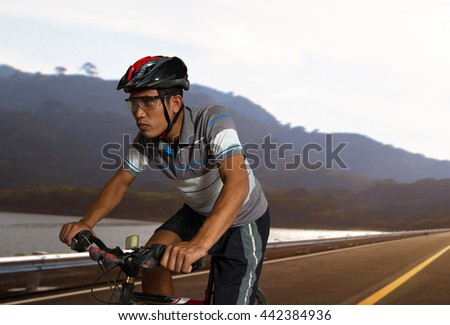 Asian men cycling exercise on road in summer sunset - Sport bike healthy lifestyle Concept - stock photo