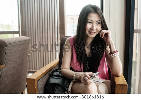 Asian middle age business woman sit in coffee shop - stock photo