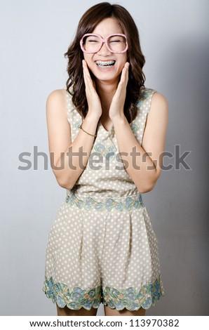 Asian model girl smiling posing on gray background - stock photo