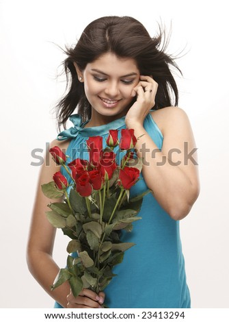 Asian modern girl talking over cellphone with bunch of red roses - stock photo