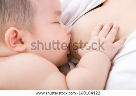 Asian mom breastfeeding her baby - stock photo
