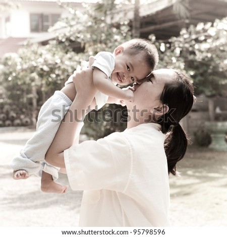 Asian mom playing with her baby - stock photo
