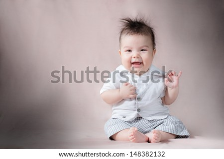 Asian 5 month old baby sitting up with wild hair and smiling with his hand up