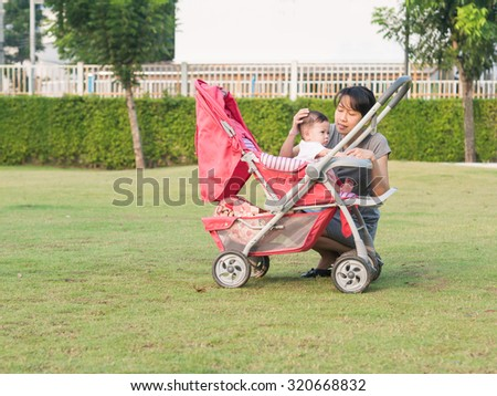 Asian mother and baby girl in stroller. - stock photo